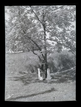Unidentified woman sitting in front of tree