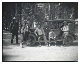 Unidentified men with automobile in forested area