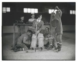 Hockey players helping goalie with gear?