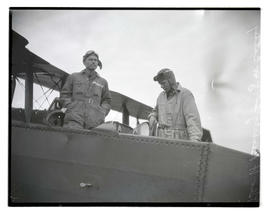 Lieutenant George H. Beverley and J. W. Cathey standing in airplane