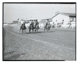 Cowboys on horseback, running down track