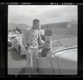 Two people with car at auto races in Tillamook, June 1955