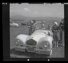 Group of people with car at auto races in Tillamook, June 1955