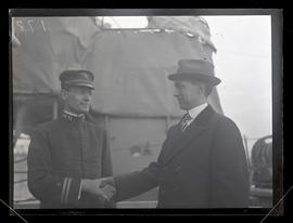 U.S. Navy officer and unidentified man shaking hands