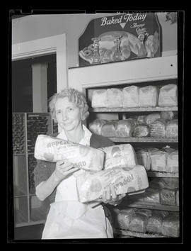 Bakery employee holding loaves of Keller's Baking Company bread