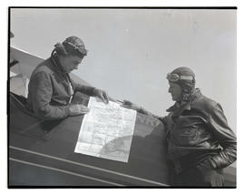 Tex Rankin and unidentified man looking at map