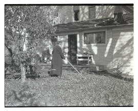 Unidentified woman in yard, using tool