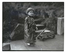 Unidentified young boy outdoors in raincoat, full-length portrait