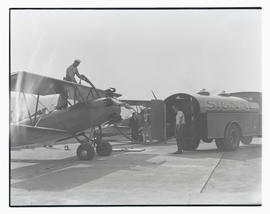 Unidentified man fueling monoplane at Swan Island airport, Portland