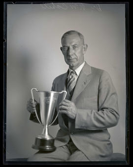 Dr. R. W. Cahill, holding golf trophy