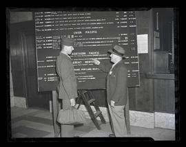 Serviceman and USO member looking at railroad schedules, Union Station, Portland