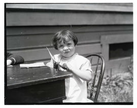Unidentified girl cutting paper at table outdoors
