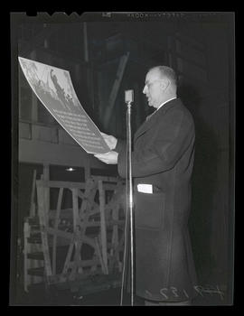 Man reading from poster during address to workers at Albina Engine & Machine Works, Portland