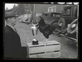 Unidentified man with rooster and trophy, probably at Pacific International Livestock Exposition