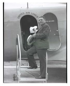 Joseph Ryan, standing on steps to airplane