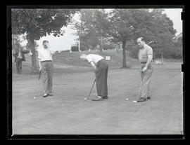 Three unidentified golfers on green