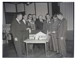 Portland Gas & Coke Co. vice president R. G. Barnett and unidentified men looking at model of...