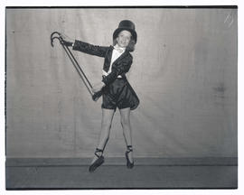 Young ballet dancer in costume, posing en pointe and holding cane