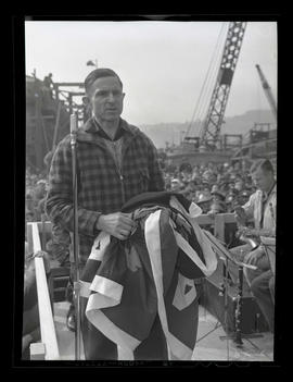 Electrician Ed Mabie holding pennant during award ceremony at Albina Engine & Machine Works, ...