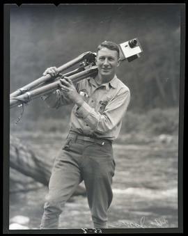 Otto Jones, standing on riverbank and carrying camera