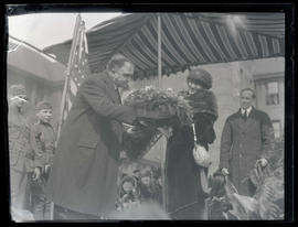 George L. Baker presenting unidentified woman with floral key to the city