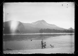 Unidentified man and girl with dogs on bank of Columbia River with view of Beacon Rock
