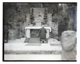 Unidentified clergyman? kneeling before altar at The Grotto, Portland
