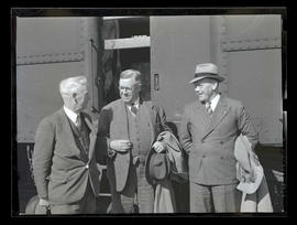 Three unidentified men next to train car, probably at Pacific International Livestock Exposition