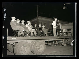 Young man speaking into a microphone on top of truck platform