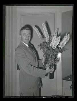 Unidentified man holding vase of flowers and prize ribbon?