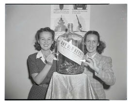 Two young women posing with keys and scrap-metal collection bottle