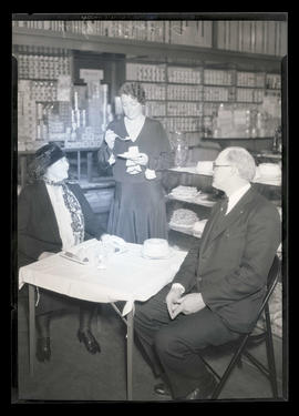 Three people with food at Sealy-Dresser Company store, Portland