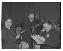 Three men performing for radio broadcast at Portland Breakfast club meeting