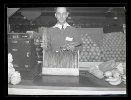 Unidentified grocery-store employee holding asparagus