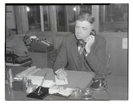 Charles F. Walker? sitting at desk and holding telephone receiver