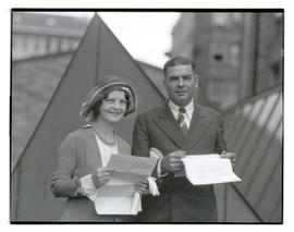 Tex Rankin and unidentified woman, both holding documents