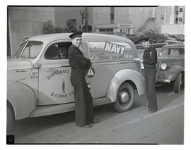 Two U. S. Navy servicemen posing with Portland Gas & Coke Co. car