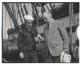 Seaman G. B. Howe of USS Constitution and Lieutenant Commander J. C. Ghormley looking at coins fr...