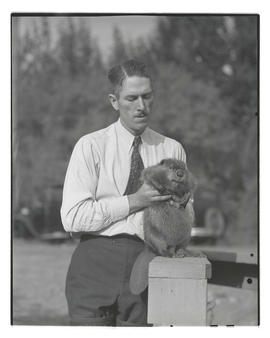 Unidentified man holding beaver, probably at Pacific International Livestock Exposition