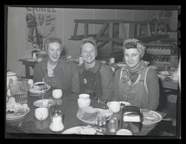 Three unidentified workers eating meal at Albina Engine & Machine Works, Portland