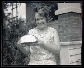 Mrs. J. F. Ball, holding loaf of bread