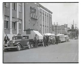 Unidentified people posing with cars and travel trailers, Southeast 6th and Alder, Portland