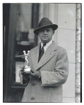 Rogaway holding basketball trophy