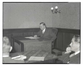Unidentified man at desk during meeting or hearing?