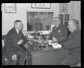 Joseph K. Carson, unidentified police captain, and Burton K. Lawson seated at desk