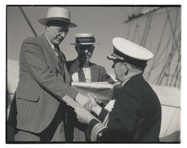 Commander Louis J. Gulliver greeting two unidentified men aboard USS Constitution?