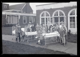Children posing outside hospital? with Santa Claus and reindeer