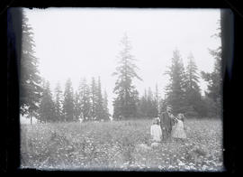 Unidentified man and two girls in meadow of wildflowers