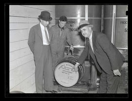 Three men with barrel at Columbia Distributing Co., Portland