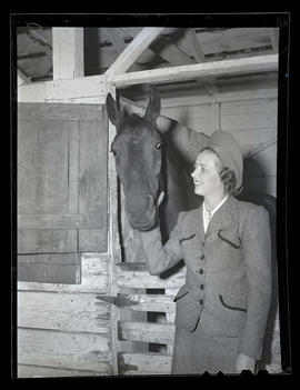 Woman in stable with horse